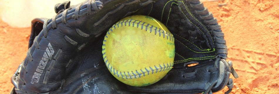 old softball glove by home plate with ball